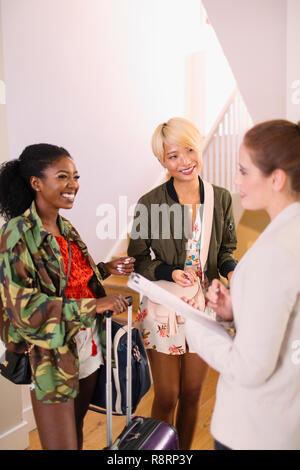 Immobilienmakler im Gespräch mit jungen Frauen mit Koffer im Haus Miete - Stockfoto