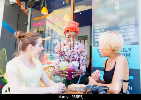 Junge Frauen, die Freunde genießen Smoothies im Straßencafé - Stockfoto