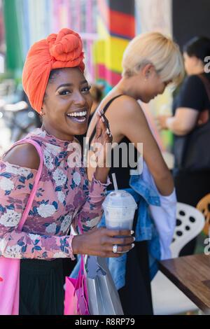 Portrait glückliche, unbeschwerte junge Frau mit Kopftuch trink Smoothie - Stockfoto