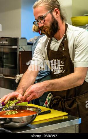Männliche Chef Schneiden Avocado für Hochzeit Essen - Küche, Text auf Schürze 'Made für Geschenke, tolle Bäckerei, Genießen' - Stockfoto