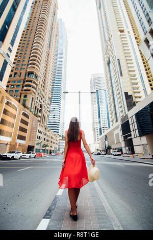 Junge Frau im roten Kleid und Strohhut zu Fuß in der Nähe von Wolkenkratzern in der modernen Stadt. Low Angle View - Stockfoto