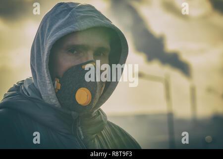 Mann, der eine wirkliche Bekämpfung der Umweltverschmutzung, anti-Smog und Viren Gesichtsmaske; dichte Smog in der Luft - Stockfoto