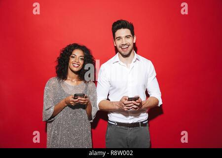 Porträt eines lächelnden Jungen elegant gekleidete Paar stehen über den roten Hintergrund isoliert, Mobiltelefone zu benutzen - Stockfoto