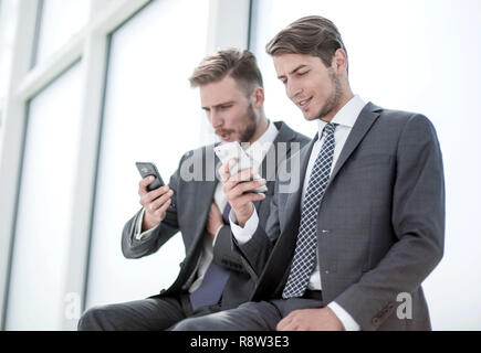 Kollegen lesen Sie Mediendateien auf ihren Smartphones. - Stockfoto