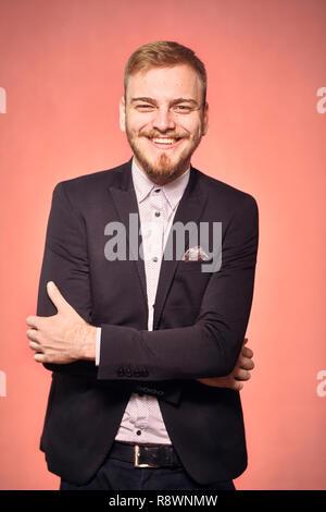 Ein junger Mann, trägt Anzug und Hemd, 20-29 Jahre alt, Kamera suchen, ehrlichen Lächeln glücklich, freundlich. Das reale Person, nicht Modell. Rosa backgr - Stockfoto
