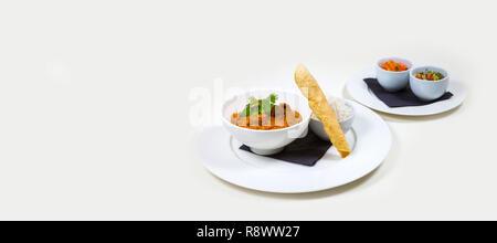 Indische Curry in einer weißen Schüssel mit Reis auf einem weißen Teller auf weißem Hintergrund - Stockfoto
