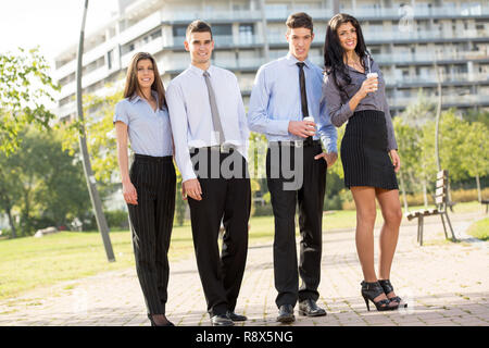 Gruppe junge erfolgreiche Geschäft Leute auf der Kaffeepause in einem Park in der Nähe ihrer Firma, deren Büro Gebäude im Hintergrund zu sehen. - Stockfoto