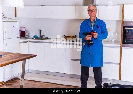 Alte Handwerker steht in der Küche in der Nähe seiner Toolbox - Stockfoto