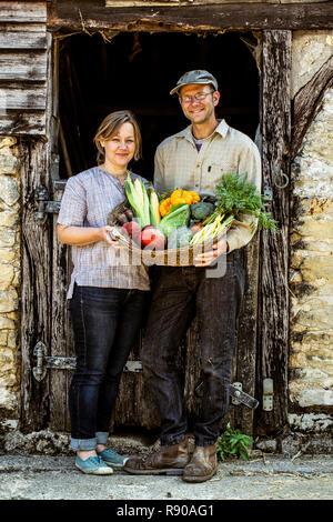 Lächelnd Bauer und Frau, die in der Scheune nebenan, Korb mit frisch geernteten Gemüse, an der Kamera schaut. - Stockfoto