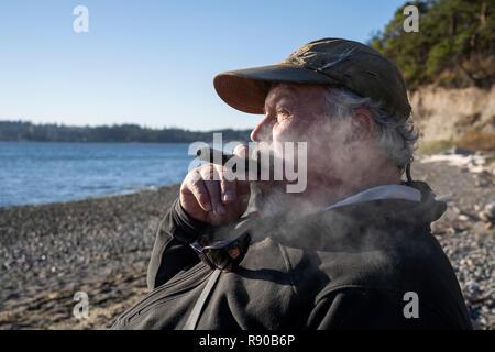 Eine Fliege Fischer genießt eine Zigarre und nimmt einen Bruch von Fliegenfischen für searun Küsten Halsabschneider Forellen und Lachs im Nordwesten von Washington State USA - Stockfoto