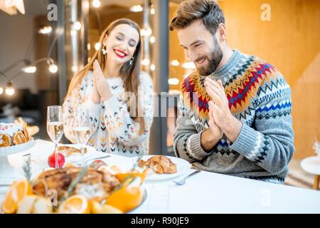 Junges Paar in festlichen Abendessen sitzen zusammen in das moderne Haus während der Winterferien - Stockfoto
