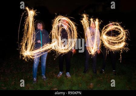 Das Wort LIEBE Dinkel von vier Menschen mit Wunderkerzen - Stockfoto