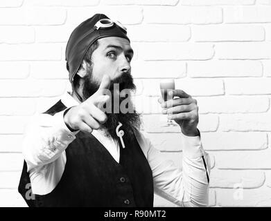 Schöne bärtige aviator Mann mit langem Bart und Schnurrbart auf überrascht Gesicht holding Glas alkoholische Schuß in Vintage Leder weste mit Hut und Brille auf der weißen Wand Hintergrund. - Stockfoto