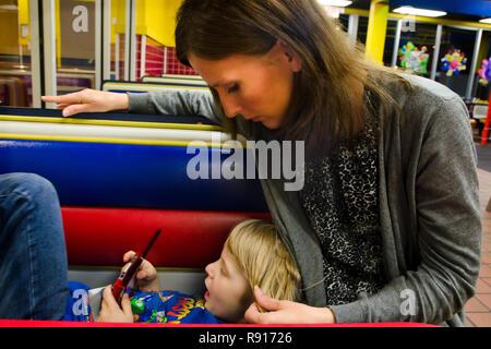Ein Junge, der hat Asperger Syndrom, einer Form von Autismus, spielt ein Spiel, wie seine Mutter seinem Haar Anschläge, 19. April 2012, in Columbus, Mississippi. - Stockfoto