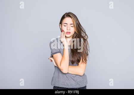 Junge Frau hat Zahnschmerzen, studio Foto auf einem grauen Hintergrund isoliert - Stockfoto