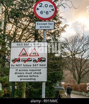 Zeichen verlassen Grasmere Dorf Warnen von Long/grosse Fahrzeuge zu vermeiden, folgende Sat Nav, der sich die steilen und schmalen roten Bank Road. - Stockfoto
