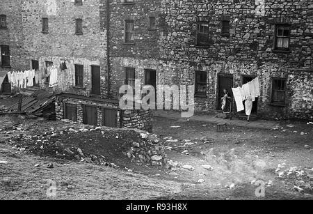 Mitte der 1940er Jahre, slum Gehäuse in Merthyr, South Wales, UK. Der Niedergang der lokalen Stahl und Kohle in den 1930er Jahren und dann wieder nach WW2 bedeutete Migration und Arbeitslosigkeit und große Armut und Not gelitten, mit schlechte Wohnverhältnisse und Lebensbedingungen. Hier sehen wir die lokalen Frauen setzen ihre Wäsche auf einer Wäscheleine außerhalb ihrer Häuser. - Stockfoto