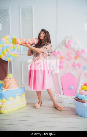 Nettes Mädchen mit rosa Donuts posiert, Aprilscherze, Dessert, schlechtes Essen, schaut in das Loch in der Donut, Donuts, die von den Augen - Stockfoto