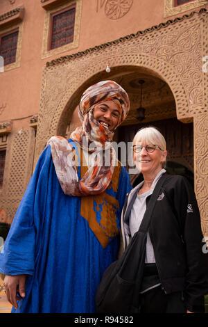 Marokko, Ouarzazate, Mann mit traditionellen Berber tribal Bekleidung mit westlichen Touristen - Stockfoto
