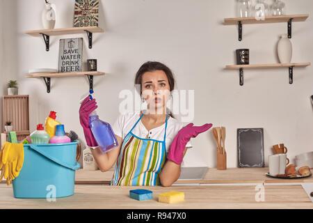 Schöne fröhliche brünette Frau in Handschuhe Reinigung, moderne Küche. Emotionale Haushälterin. Schüssel voller Flaschen mit Desinfektionsmittel auf Tisch - Stockfoto