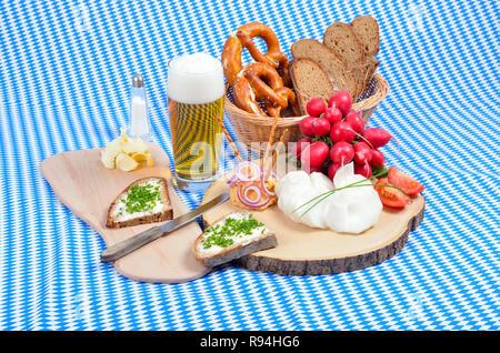 """Bayerische Snack mit Spezialität """"obazda"""", serviert mit Zwiebelringen, Brezeln und Radieschen auf einem hölzernen Platte - Stockfoto"""