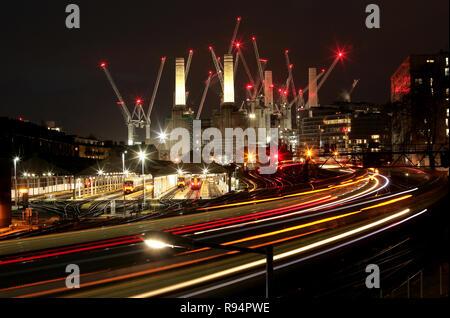 Battersea Power Station in der Nacht mit Kränen und Züge. Vom Bahnhof Victoria gesehen. Apple Campus.