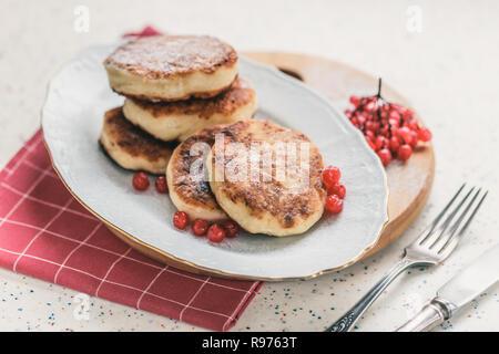 Auf einem weißen Tisch aus Kunststein ist ein Holz Schneidebrett mit fünf Quark Pfannkuchen und rote Beeren. - Stockfoto
