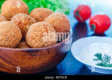 Falafel liegt in einer Holzplatte. Auf dem Tisch liegen, Tomaten, Gurken, Salat, Dill, Zitrone, saure Sahne. - Stockfoto