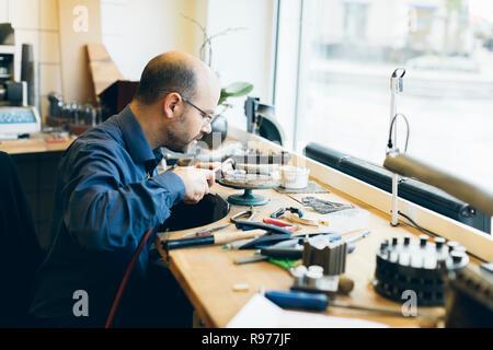 Goldschmied arbeiten mit einer Lötlampe in seiner Werkstatt in Schweden - Stockfoto