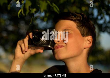 Junge Fotograf mit retro Film Foto Kamera im Garten. Der Junge hält eine Kamera in den Händen und nimmt Bilder von Bäumen - Stockfoto
