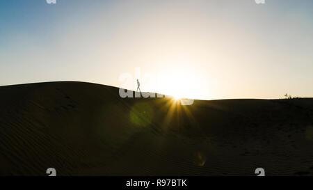 Silhouette eines Mannes zu Fuß auf einer Düne mit Sonne, Einstellung, Jaisalmer Wüste, Rajasthan, Indien - Stockfoto