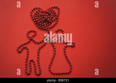 Kreative Idee auf einem roten Hintergrund der Perlen ein Mann und eine Frau halten zusammen eine Hand und zwischen ihnen ein Herz. Festliche Konzept für den Valentinstag. - Stockfoto