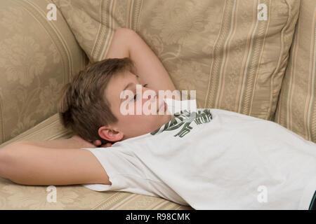 Lethargisch gelangweilte mürrisch Moody faul zwoelfjaehriger Junge Festlegung auf ein Sofa - Stockfoto