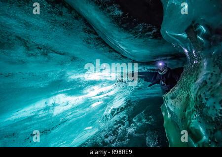 Karen Rentz in einer Eishöhle innerhalb einer Nocke der Gletscher Myrdalsjökull, die auf Katla Vulkan sitzt, im Winter in Island - Stockfoto