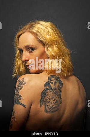 Eine junge blonde Mädchen mit einem tätowierten zurück - Stockfoto