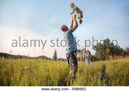 Verspielt Vater werfen baby Sohn Overhead in sonniger, ländlichen Bereich - Stockfoto