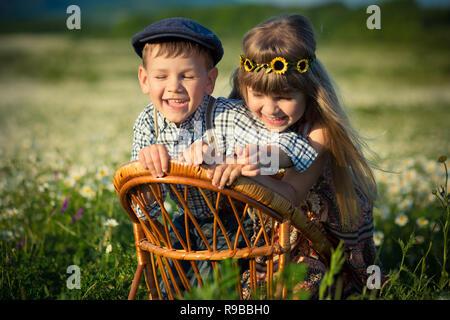 Cute schöner Junge in Jeans und Shirt sittingand Spielen auf holzstuhl zusammen mit schönen Mädchen auf der Wiese von Gänseblümchen Gänseblümchen und lächelnd e - Stockfoto