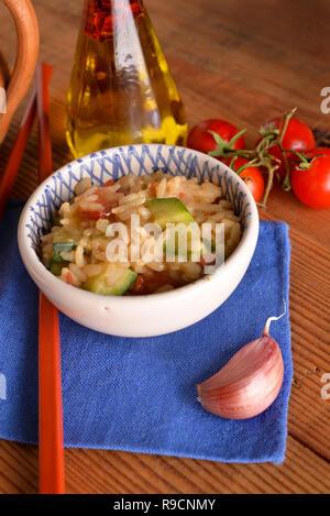 Schalen von Reis mit Cherry Tomaten und Zucchini auf Holz - Stockfoto