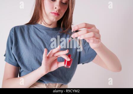 Foto zuschneiden der Jungen cute Teen Girl Farben Nägel auf grauem Hintergrund - Stockfoto