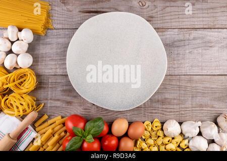 Pasta, Gemüse, Eier, mit Teller in der Mitte auf Holz- Hintergrund - Stockfoto