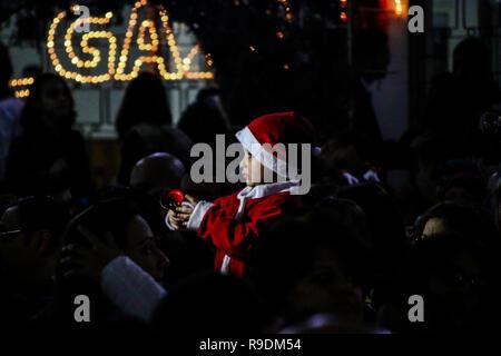 Gaza, Palästina. 22. Dez 2018. Das YMCA im Gazastreifen den Weihnachtsbaum Zeremonie in seinen Platz in Gaza Stadt organisieren am Abend des 22. Dezember 2018. Eine palästinensische Folklore tanzen und den Segen eines griechisch-orthodoxen Patriarchen begleitet die Zeremonie in der bis zum Heiligabend. Christliche und muslimische Palästinenser converged auf dem Platz in Gaza zu feiern und den Dekorationen und andere Traditionen der Jahreszeit, wie Fotos der Kinder mit Santa Claus und Nächstenliebe Sammlungen für die Bedürftigsten zu genießen. Credit: ZUMA Press, Inc./Alamy leben Nachrichten