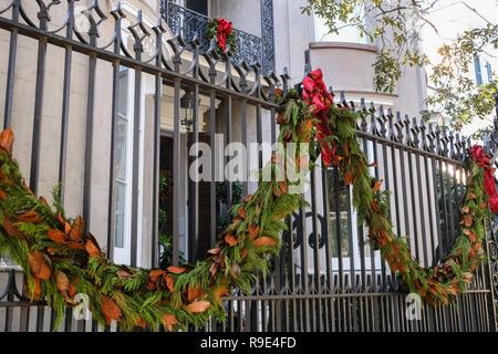 Traditionelle magnolia roping schmückt das eiserne Tor Eingang zu einem historischen Haus für die Weihnachtsfeiertage auf Sitzung Straße in Charleston, South Carolina. - Stockfoto