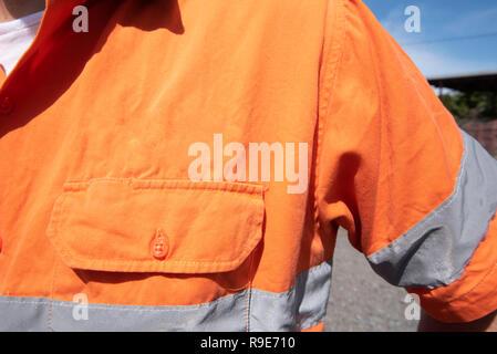 In der Nähe der linken Schulter vor Brust Tasche auf einer hohen Sichtbarkeit (Hi Vis) orange Arbeit Shirt ohne Beschriftung - Stockfoto