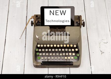 """Konzept der Technologie Fortschritt - alte Schreibmaschine und neuen Tablet-PC mit Worten """"neue Technologien"""" auf hölzernen Hintergrund - Stockfoto"""