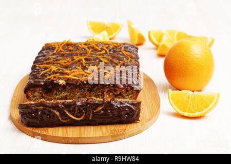 Schokolade und Orange mit einem Stück Kuchen Abschneiden in der Nähe von Orange auf weißem Holz- Hintergrund. Flache konzentrieren. - Stockfoto