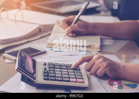Business Konzeption: Nahaufnahme, Frau, Hand mit Taschenrechner und schreiben Sie mit am Büro Schreibtisch berechnen. - Stockfoto
