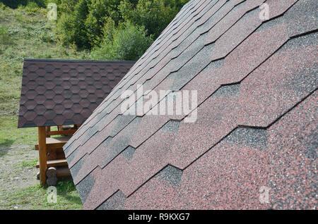 Die Beschaffenheit des Daches mit bituminösen Beschichtung. Grobe bituminösen Mosaik von Rot und Braun Blumen. Wasserdichtes Dach - Stockfoto