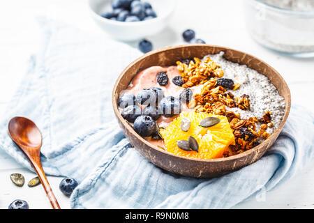 Vegan smoothie Schüssel mit Chia Pudding, Beeren und Müsli in einem coconut Shell auf einem weißen Holz- Hintergrund. Auf Basis pflanzlicher Ernährung Konzept. - Stockfoto