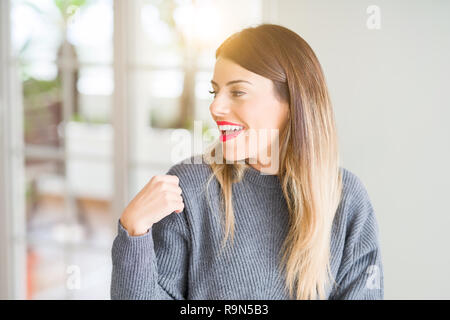 Junge schöne Frau winter Pullover zu Hause weg schauen mit einem Lächeln auf dem Gesicht zu Seite, natürlicher Ausdruck. Lachend zuversichtlich. - Stockfoto