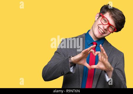 Junge schöne business Mann mit roten Gläsern über isolierte Hintergrund in der Liebe mit Herz und mit Hand lächelnd. Romantische Konzept. - Stockfoto